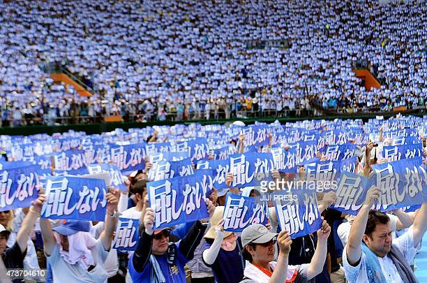 Some 35000 protesters raise placards saying 'Do not yield to authority' during a rally to protest against a controversial US airbase in Naha in...