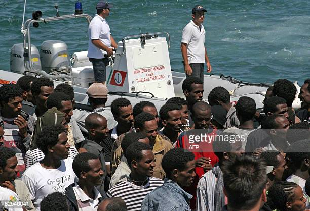 Some 355 wouldbe immigrants from Eritrea arrive by boat in the port of Italy's southern island of Lampedusa late on 21 August 2008 Nearly 500 boat...