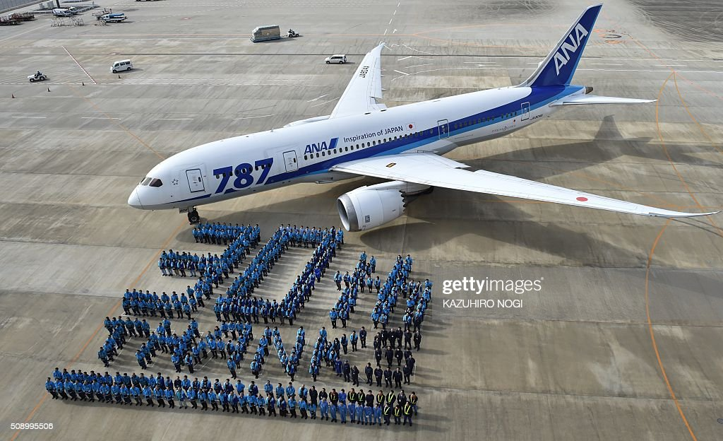Some 388 employees of Japan's All Nippon Airways (ANA) Group companies and its partner companies stand in formation that reads '30th thanks' in front of a Boeing 787 aircraft in front of a hangar at Narita International Airport in Chiba prefecture on February 8, 2016. ANA will celebrate its 30th anniversary since its first regular international flights this upcoming March 3. AFP PHOTO / KAZUHIRO NOGI / AFP / KAZUHIRO NOGI