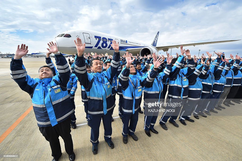 Some 388 employees of Japan's All Nippon Airways (ANA) Group companies and its partner companies stand in formation in front of a Boeing 787 aircraft in front of a hangar at Narita International Airport in Chiba prefecture on February 8, 2016. ANA will celebrate its 30th anniversary since its first regular international flights this upcoming March 3. AFP PHOTO / KAZUHIRO NOGI / AFP / KAZUHIRO NOGI