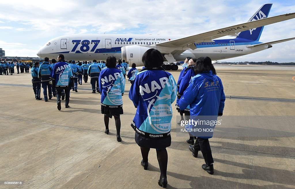 Some 388 employees of Japan's All Nippon Airways (ANA) Group companies and its partner companies gather to stand in formation in front of a Boeing 787 aircraft in front of a hangar at Narita International Airport in Chiba prefecture on February 8, 2016. ANA will celebrate its 30th anniversary since its first regular international flights this upcoming March 3. AFP PHOTO / KAZUHIRO NOGI / AFP / KAZUHIRO NOGI