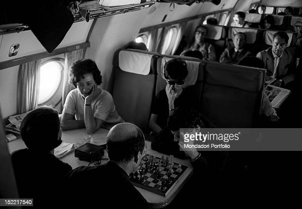Some actors of the Teatro alla Scala company are relaxing by chatting and playing chess during air travel September 1964