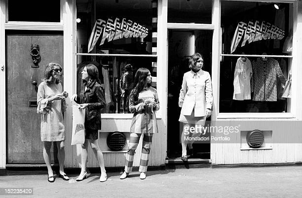 Some British girls waiting in front of 'Palisades' boutique The Pauline Fordham shop sign has been designed by the pop artist Derek Boshier London...