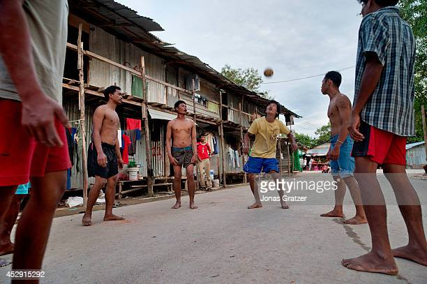 Some Burmese migrant workers enjoy playing footvolley in their seperate area next to the construction site that they work on in Phuket Thailand these...