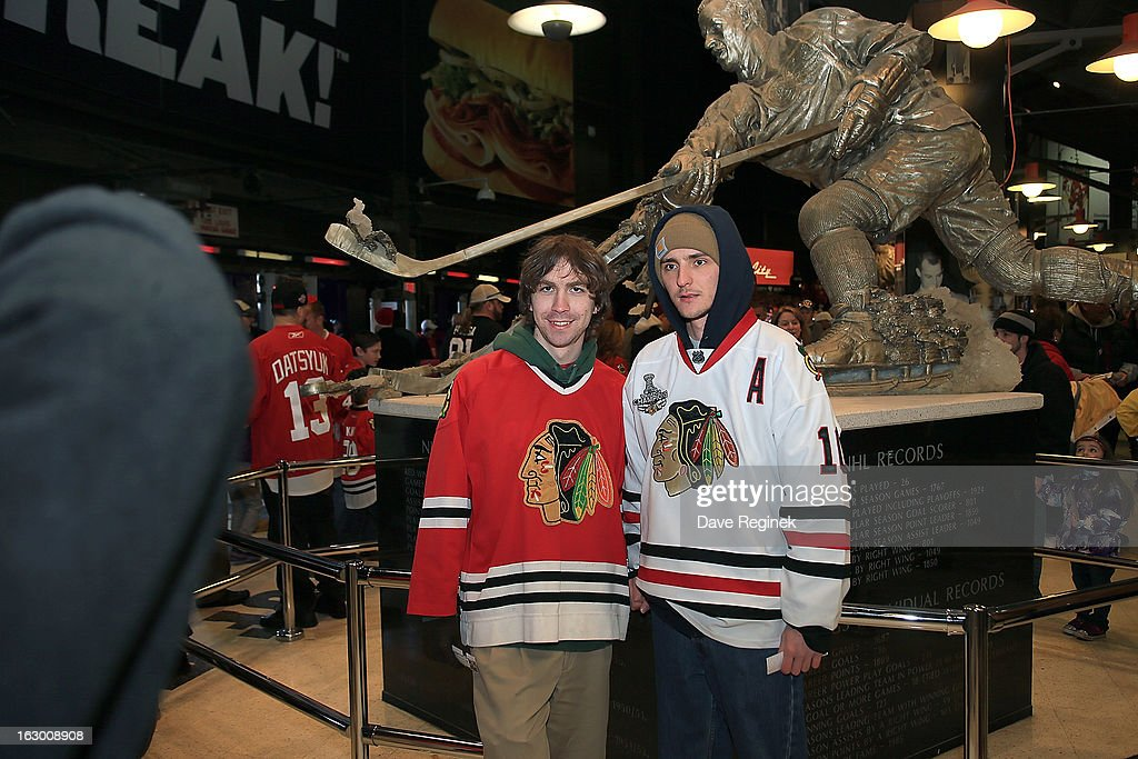 Some Chicago Blackhawks fans pose for a picture in front of the Gordie Howe statue in the concourse of Joe Louis Arena before an NHL game against the Detroit Red Wings on March 3, 2013 in Detroit, Michigan.