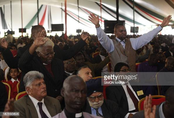 Some Christian worshipers raise their hands as people attend a special interreligious prayer service for the victims of the Westgate shopping mall...