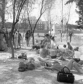'Some dancers working for the film 'Cleopatra' relaxing on the grass around Cinecitt during a break In the background a pyramidshaped structure ready...