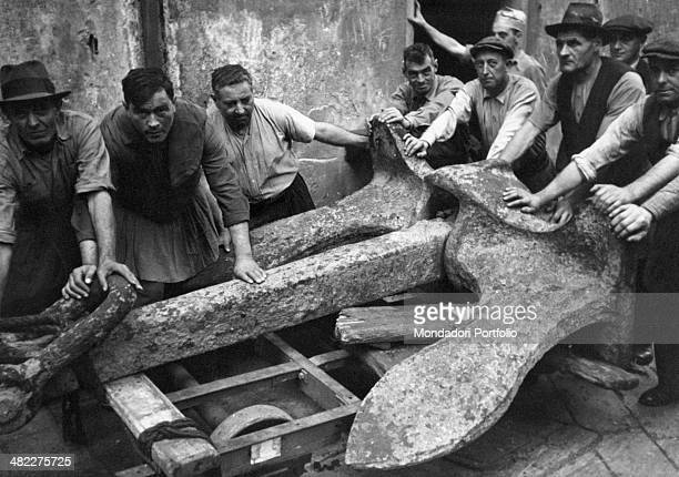 Some dock workers posing around an anchor at the Port Genoa 1950s