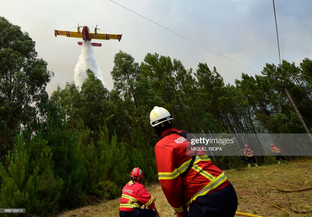 TOPSHOT - Some firefighters prepare themselves to be overflied by a Canadair firefighting plane droping its water load on a wildfire in Vale da Ponte, Pedrograo Grande, on June 20, 2017. The huge forest fire that erupted on June 17, 2017 in central Portugal killed at least 64 people and injured 135 more, with many trapped in their cars by the flames. PHOTO / Miguel RIOPA