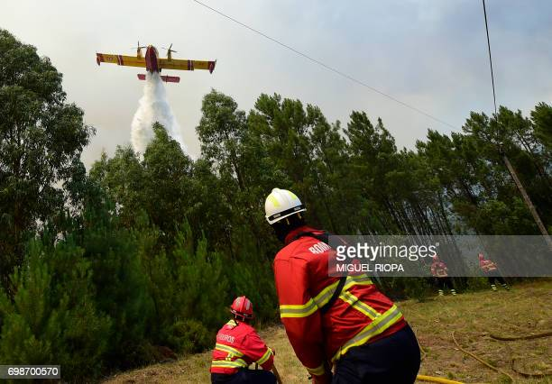 TOPSHOT Some firefighters prepare themselves to be overflied by a Canadair firefighting plane droping its water load on a wildfire in Vale da Ponte...