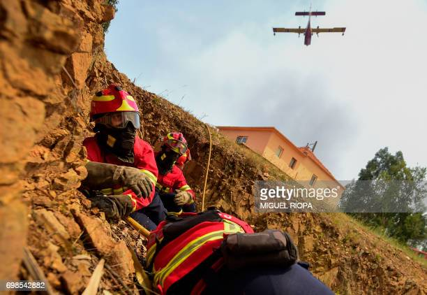TOPSHOT Some firefighters protect themselves as a Canadair firefighting plane drops its load on a wildfire in Vale da Ponte Pedrograo Grande on June...