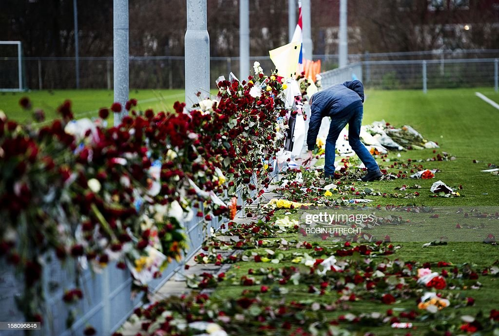 Some hours before the cremation of Dutch linesman Richard Nieuwenhuizen, a man looks at the flowers at his memorial site by the clubhouse of Dutch soccer club SC Buitenboys in Almere, Netherlands, on December 10, 2012. The linesman of the club SC Buitenboys in Almere died on 3 December after he was allegedly beaten by teenage players of SV Nieuw Sloten following a match on 2 December 2012. AAFP PHOTO/ ROBIN UTRECHT netherlands out