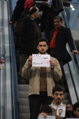 Some Iranian students hold photo of assassinated nuclear scientist Mostafa AhmadiRoshan and his boy as they protest at the Imam Khomini' airport in...