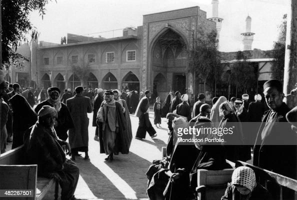 Some Iraqi people walking in a street near the Husayn Mosque Karbala December 1956