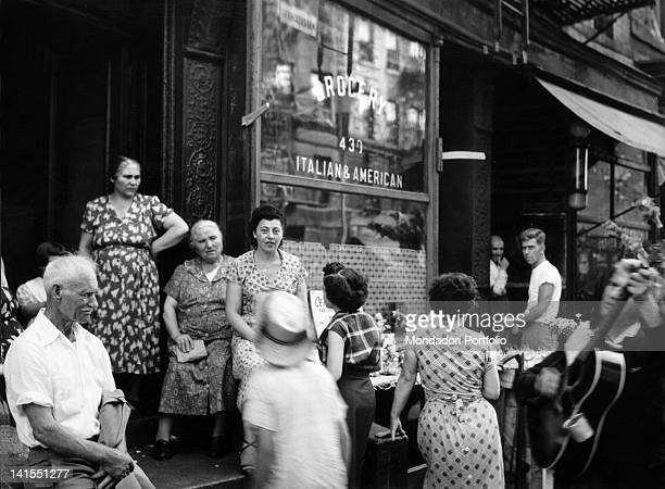 Some Italian American women conversing with each other in front of a grocery store in Little Italy New York 1950s