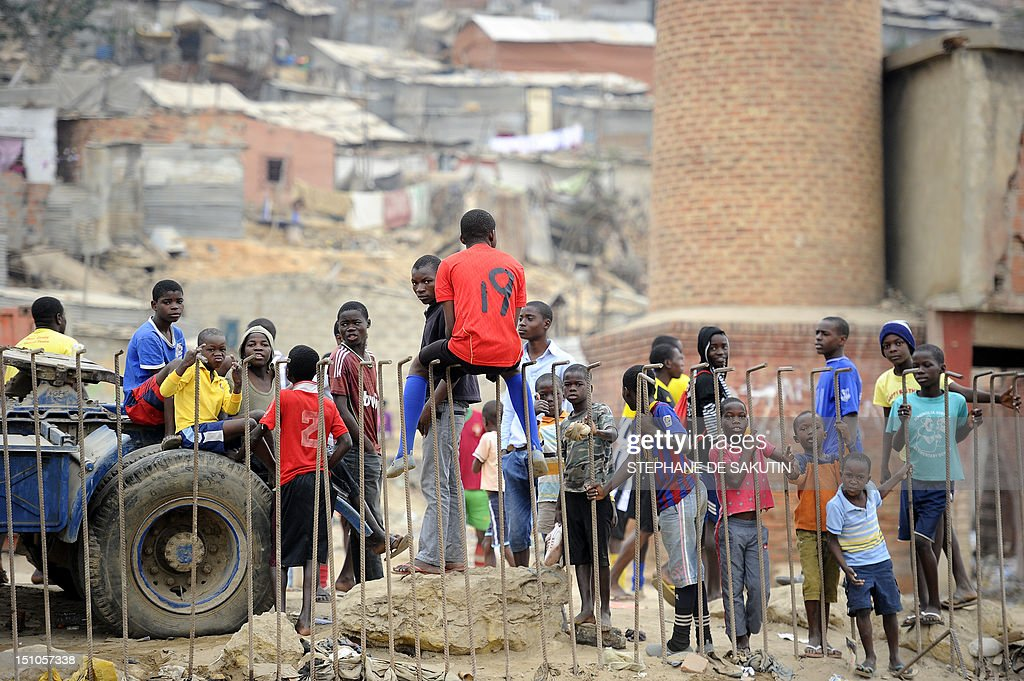 Some kids stand at the Boa Vista slum, in the outskirts of Luanda, on August 31, 2012. The ruling Popular Movement for the Liberation of Angola party (MPLA) of President Jose Eduardo dos Santos, which has been in power since independence 37 years ago, compete today in the legislative poll against 8 other political parties, including the main opposition Union for the Total Independence of Angola (UNITA). Dos Santos promised that with a new term he would push ahead with his multi-billion-dollar drive to rebuild the country after the civil war that ended a decade ago. MPLA is widely expecting to win the elections and beat the UNITA former rebel movement which does not have the same access to funds or the state-controlled media. AFP PHOTO / STEPHANE DE SAKUTIN