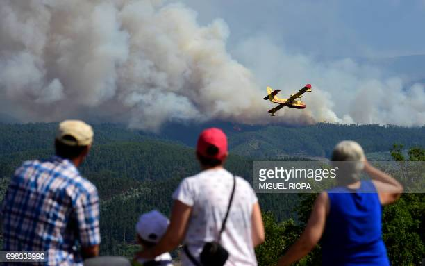 TOPSHOT Some locals watch a Canadair plane overflying smoke columns taht raise as wildfires burn close to Pedrogao Pequeno on June 20 2017 The huge...