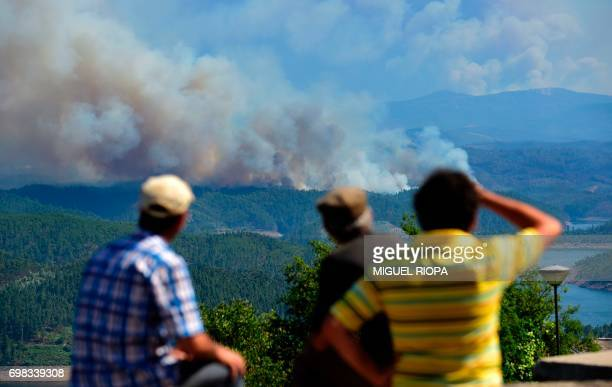 Some locals watch moke columns raising as wildfires burn close to Pedrogao Pequeno on June 20 2017 The huge forest fire that erupted on June 17 2017...