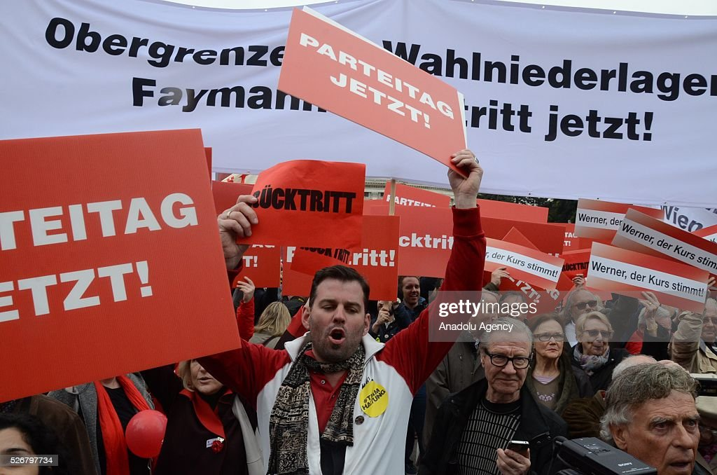 Some members of Social Democratic Party holding banners saying 'Resign' and 'Now, it is time for congress' chant slogans against Chancellor of Austria Werner Faymann during a rally to mark May Day, International Workers' Day, in front of municipal building in Vienna, capital city of Austria on May 1, 2016.