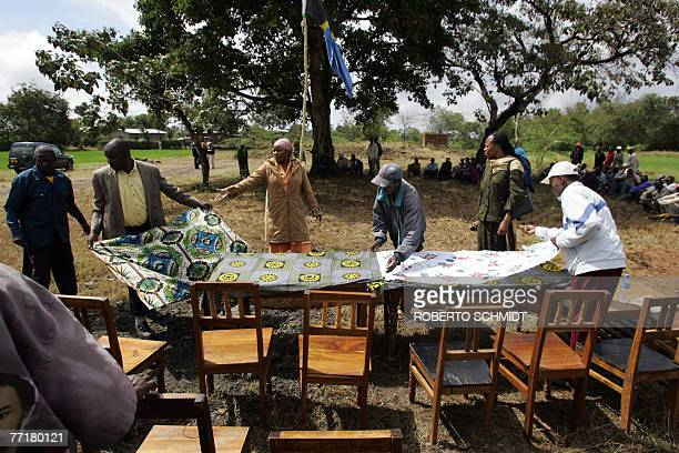Some members of the Usa River village near Arusha sit under a tree as they watch others set up a table in preparation for the reception of Princess...