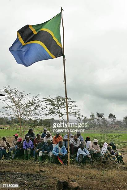 Some members of the Usa River village near Arusha Tanzania sit patiently on rocks near a Tanzanian flag as they wait for the arrival of Princess...