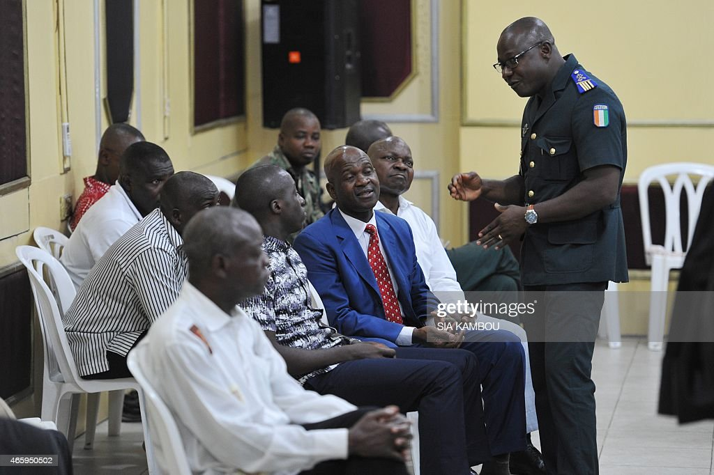 Some of 14 members of ex-President Laurent Gbagbo's security detail wait on March 12, 2015 to stand trial before a military court in Abidjan over post-election violence that killed some 3,000 people. The military trial comes after a civilian court on March 10 sentenced former first lady Simone Gbagbo to a 20-year prison term on charges of undermining state security during the 2010-2011 crisis. The former president himself is in The Hague awaiting trial in July for crimes against humanity at the International Criminal Court. AFP PHOTO / SIA KAMBOU