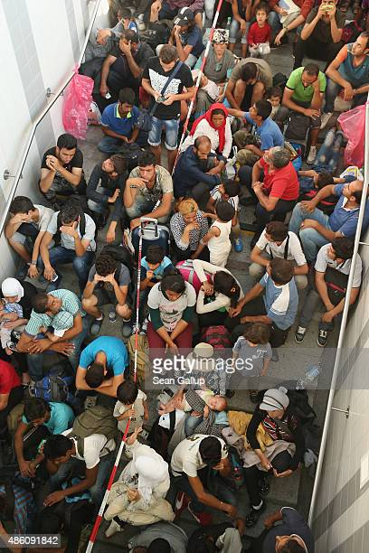 Some of approximately 190 migrants who arrived on a train from Budapest and were detained by German police at Rosenheim railway station wait to be...