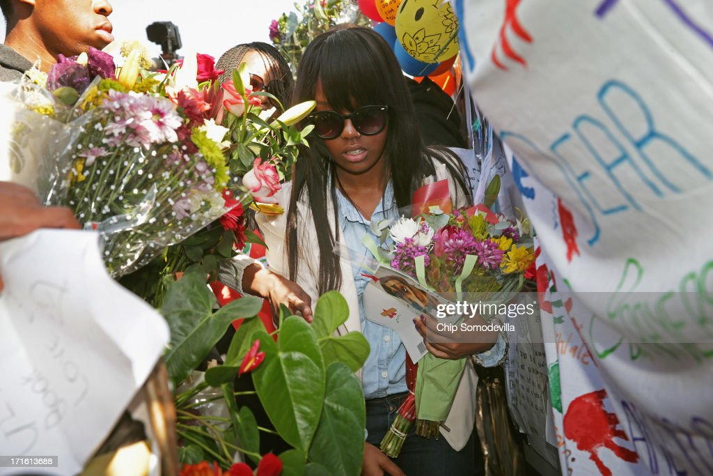 Some of former South African President Nelson Mandela's grand children and great-grandchildren collect flowers left by supporters outside the Mediclinic Heart Hospital where Mandela is being treated for a recurring lung infection on June 27, 2013 in Pretoria, South Africa. President Jacob Zuma is scheduled to make an announcement to the country at noon today.