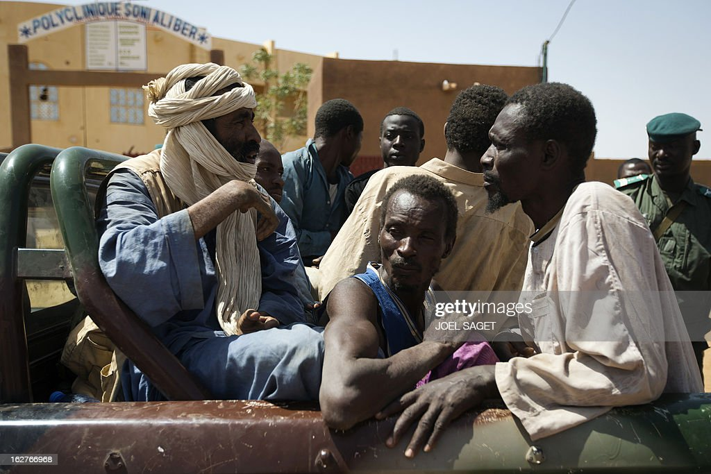 Some of nine prisoners, comprising seven Malian, one Nigerois and one Mauritanian, are taken out of a jail at the gendarmerie in the northern Malian city of Gao on February 26, 2013 to be transferred on a military flight to Bamako, where they are to be judged on charges of belonging to the main Islamist armed group, the Movement for Oneness and Jihad in West Africa (MUJAO), an Al-Qaeda offshoot. French and Malian government forces reconquered on January 26 the city opf Gao, two weeks after Paris launched an offensive in the north.
