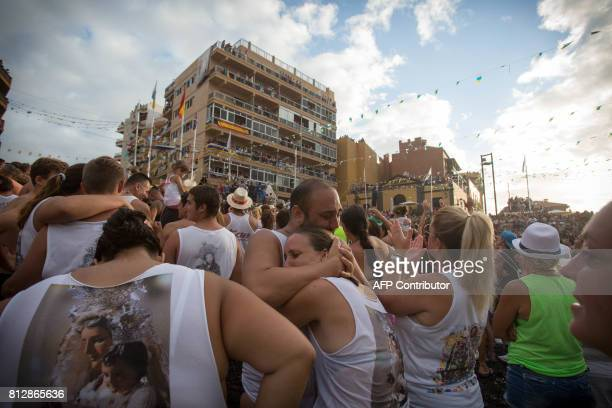 Some of the 35000 people who attended the Virgin of the Carmen Ship arrival at the Port of La Cruz cry and embrace during the arrival of the image on...