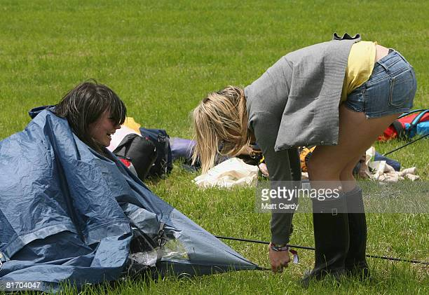 Some of the first festival revellers attempt to set up their tent in the wind as they arrive at the Glastonbury Festival at Worthy Farm Pilton on...