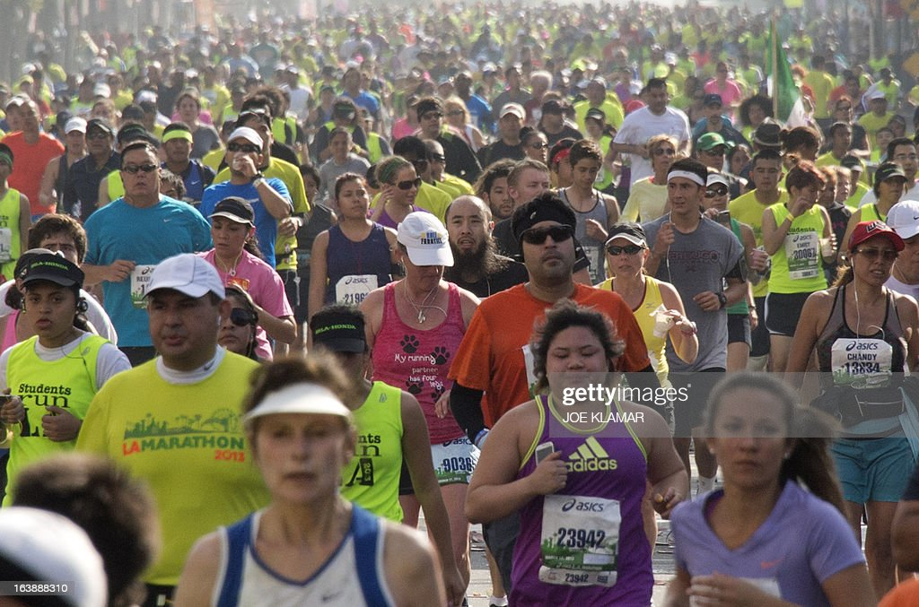 Some of the thousands of participants running down Hollywood boulevard during the annual Asics LA Marathon on March 17, 2013 in Hollywood , California. The marathon, attended by over 24 thousand participants, started at Dodger's stadium in Los Angeles and finished in Santa Monica pier. AFP/JOE KLAMAR
