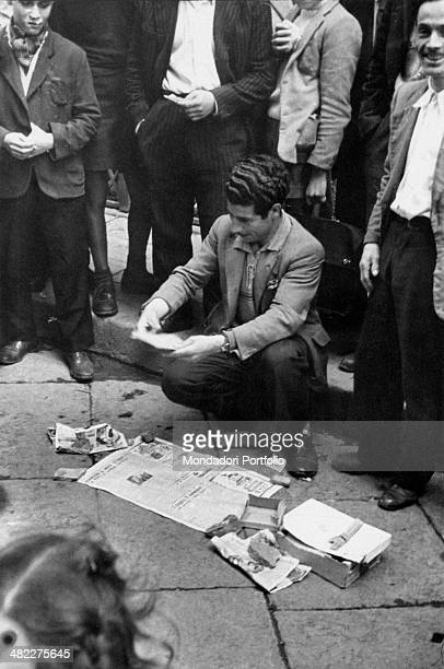 Some passersby having fun by looking at a man building a game on the streets of the city Naples 1950s