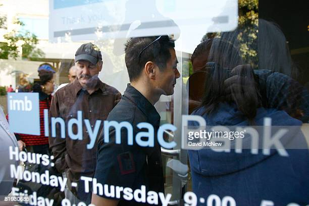 Some people are allowed through the doors after waiting in line with hundreds of other customers to get into an IndyMac Bank open for the first time...
