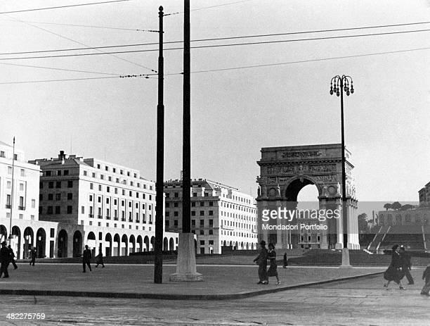 Some people crossing piazza della Vittoria with the War memorial Arch designed by Marcello Piacentini and Arturo Dazzi in the middle Genoa 1950s