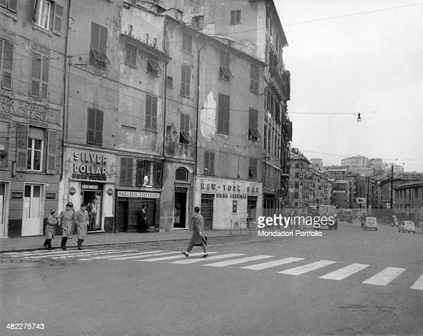 Some people crossing via Antonio Gramsci on the zebra crossing There are the signs of the Albergo Ristorante Universo the Silver Dollar café a...
