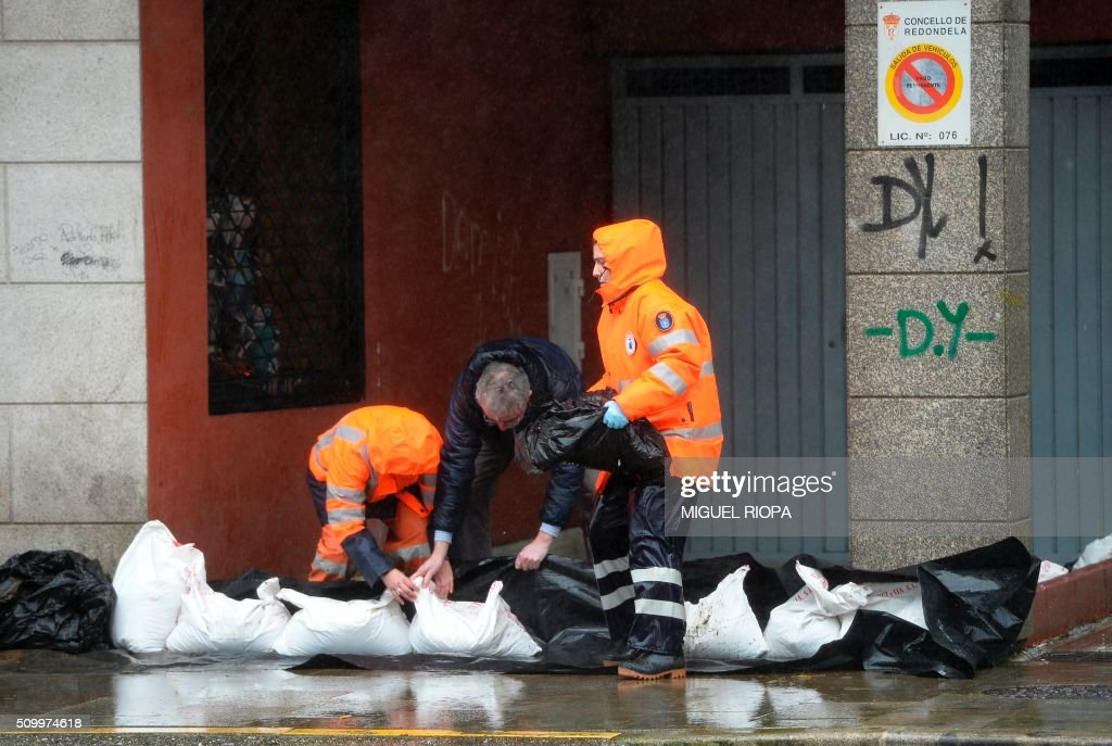 Some people put up a sack bags barrier in a flooded area next to the river Tea in Ponteareas, northwestern Spain, on February 13, 2016. / AFP / AFP or licensors / MIGUEL RIOPA