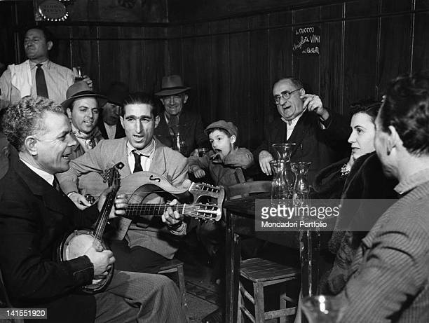 Some people singing accompanied on banjo and guitar at 'Da Checco' tavern Rome 1950s