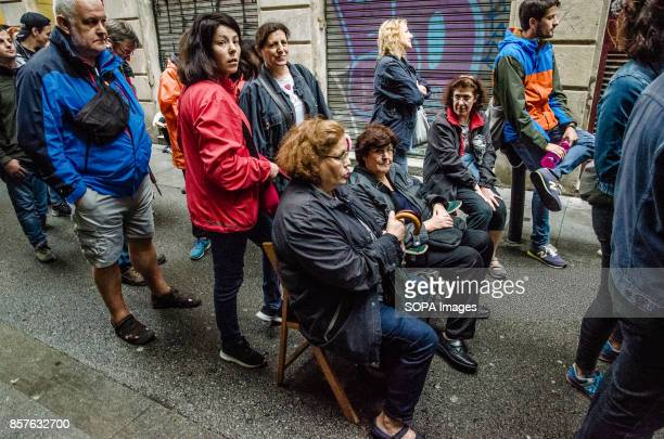 Some people sitting in chairs waiting for the referendum result Catalonia hosted its independence referendum on 1st October 2017 despite the Madrid...