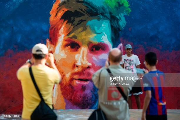 Some people take photos of a graffiti portraying Barcelona's Argentinian forward Lionel Messi on June 17 2017 in Barcelona / AFP PHOTO / Josep LAGO