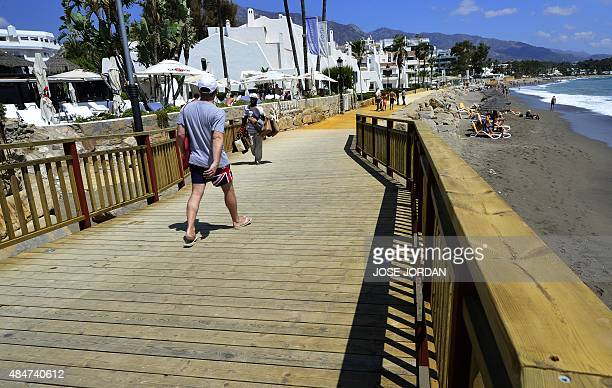 Some people walk along a wooden footbridge in Marbella's Puerto Banus marina on August 21 included in the first stage of the Vuelta a Espana cycling...