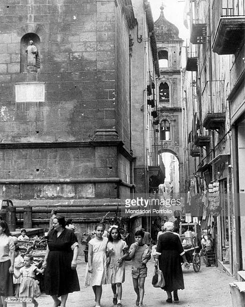 Some people walking in the street in via San Gregorio Armeno in Naples Naples 1961