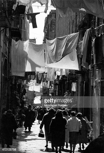 'Some people walking on Via San Gregorio Armeno the street in Naples town centre well known for the Christmas creche workshops Naples 1960 '