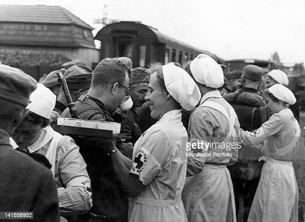 Some Red Cross nurses giving hot beverages to the passing soldiers in a sorting station of the German army Poland September 1939