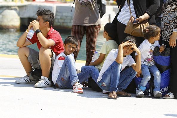 Some refugee children sit on the ground in Piraeus harbour,...