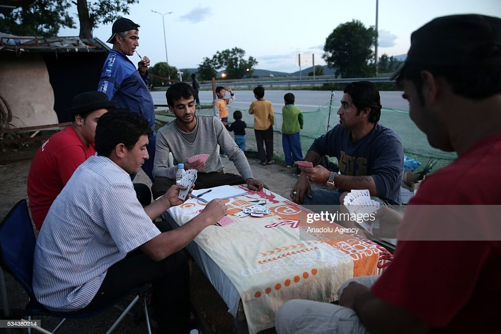 Some refugees, escaping from the evacuation in Idomeni, play cards as they wait at another refugee camp near Idomeni, Greece on May 25, 2016.