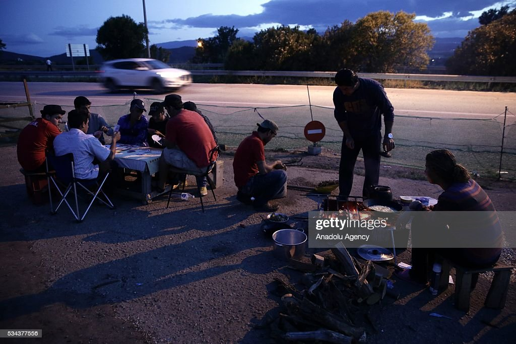 Some refugees, escaping from the evacuation in Idomeni, prepare their meal as they wait at another refugee camp near Idomeni, Greece on May 25, 2016.