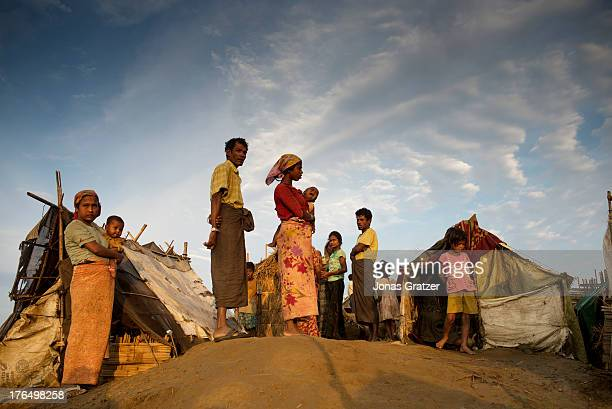 Some refugees of the Rohingya IDP camp of Sittwe attempt to warm themselves up in the morning sun after a long cold night in their makeshift tents...