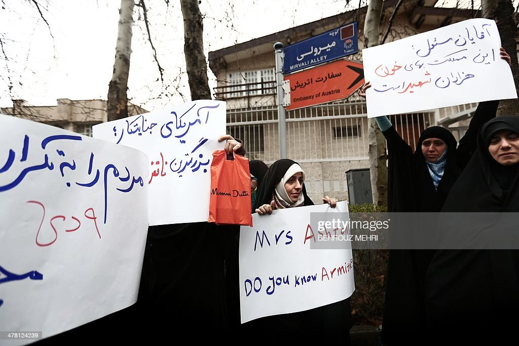 Some sixty Iranian members of the Basij militia hold slogans against EU foreign affairs chief Catherine Ashton during a protest outside the Austrian...
