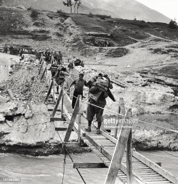 Some soldiers are passing on the gangway on Vojussa river near Premeti which has been just implemented to facilitate the offensive on the Greek front...